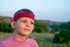 Knappe jonge jongen die in de afstand staren Royalty-vrije Stock Foto