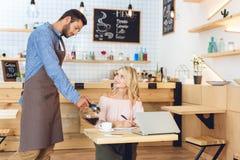 knappe jonge kelners gietende koffie aan glimlachende vrouw stock fotografie