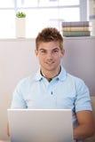 Knappe jonge kerel met laptop en oortelefoons Royalty-vrije Stock Foto's