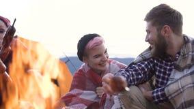 Knappe jonge man en vrouwen kokende worsten op de brand tijdens het rusten na reis stock footage
