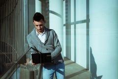 Knappe jonge mens die bij computer werkt en aan muziek luistert Royalty-vrije Stock Afbeeldingen