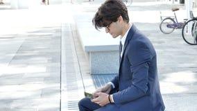 Knappe jonge mens die bij tabletcomputer werken openlucht stock videobeelden