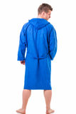 Knappe jonge mens die blauwe geïsoleerde badjas dragen, Stock Foto's