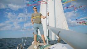 Knappe jonge mens, die captait van dit jacht is, die op kabel aan zeil in het overzees in zomer vertrekken stock footage