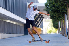 Knappe jonge mens die in de straat met een skateboard rijden Stock Afbeelding