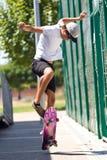 Knappe jonge mens die in de straat met een skateboard rijden Royalty-vrije Stock Fotografie