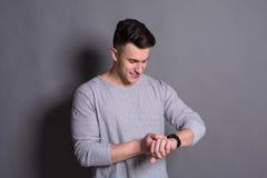 Knappe jonge mens die de tijd van het handhorloge controleren Stock Afbeelding