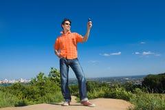 Knappe jonge mens die een beeld van de celtelefoon verzendt Royalty-vrije Stock Afbeeldingen