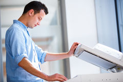 Knappe jonge mens die een exemplaarmachine met behulp van royalty-vrije stock foto
