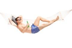 Knappe jonge mens die in een hangmat liggen Royalty-vrije Stock Fotografie