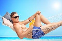 Knappe jonge mens die een oranje cocktail houden Royalty-vrije Stock Afbeeldingen