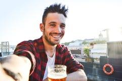 Knappe jonge mens die een selfie nemen die een bier drinken bij de bar royalty-vrije stock fotografie