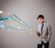 Knappe jonge mens die een telefoon met kleurrijke abstracte pijlen houden Royalty-vrije Stock Afbeelding
