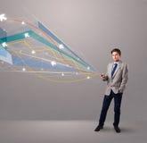 Knappe jonge mens die een telefoon met kleurrijke abstracte pijlen houden Royalty-vrije Stock Afbeeldingen
