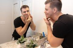 Knappe Jonge Mens die en Zijn Baard en Gezicht in Zijn Spiegel van de Huisbadkamers in de Ochtend onderzoeken die Klaar voor een  royalty-vrije stock afbeelding