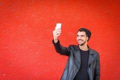Knappe jonge mens die foto op een rode achtergrond nemen Royalty-vrije Stock Foto