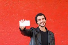 Knappe jonge mens die foto op een rode achtergrond nemen Royalty-vrije Stock Afbeeldingen