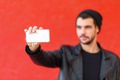 Knappe jonge mens die foto op een rode achtergrond nemen Stock Fotografie