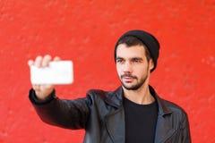Knappe jonge mens die foto op een rode achtergrond nemen Stock Foto