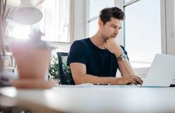 Knappe jonge mens die laptop met behulp van stock foto's