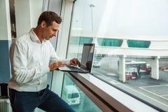 Knappe jonge mens die met laptop in luchthaven werken wanneer het wachten op zijn vliegtuig royalty-vrije stock foto's