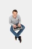 Knappe jonge mens die met laptop omhoog kijkt Stock Foto
