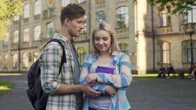 Knappe jonge mens die met mooi blonde dichtbij universiteit, studenten, het samenkomen flirten stock videobeelden