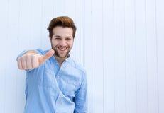 Knappe jonge mens die met omhoog duimen glimlachen stock foto's