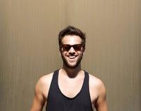 Knappe jonge mens die met zonnebril glimlachen stock fotografie