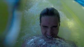 Knappe jonge mens die onderaan waterdia glijden stock videobeelden