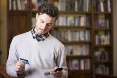 Knappe jonge mens die online op mobiele telefoon winkelen Stock Foto