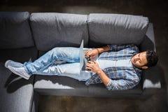 Knappe jonge mens die op bank liggen en laptop, kleine bedrijfsmensenconcept met behulp van Stock Fotografie