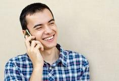 Knappe jonge mens die op de telefoon spreekt Stock Afbeelding