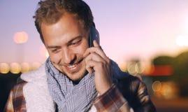 Knappe jonge mens die op slimme telefoon bij de herfstzonsondergang spreken in c Royalty-vrije Stock Foto