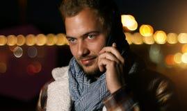 Knappe jonge mens die op slimme telefoon bij de herfstzonsondergang spreken in c Royalty-vrije Stock Afbeeldingen