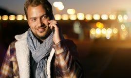 Knappe jonge mens die op slimme telefoon bij de herfstzonsondergang spreken in c Stock Fotografie