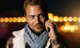 Knappe jonge mens die op slimme telefoon bij de herfstzonsondergang spreken in c Royalty-vrije Stock Fotografie
