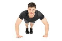 Knappe jonge mens die opdrukoefeningen doet Stock Foto's