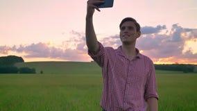 Knappe jonge mens die selfie nemen en zich op tarwe of roggegebied, mooie roze zonsondergang op achtergrond bevinden stock footage