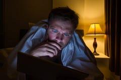 Knappe jonge mens die thuis met tabletpc lezen die op bed bij nacht liggen Hij is vermoeid en wil slapen royalty-vrije stock afbeeldingen