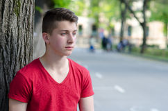 Knappe jonge mens die zich naast boom openlucht in de lente bevinden Royalty-vrije Stock Afbeeldingen