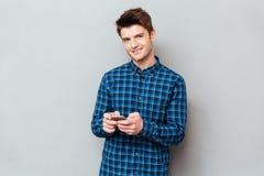 Knappe jonge mens die zich over grijze muur en het babbelen bevinden stock fotografie
