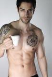 Knappe jonge mens die zijn ochtendkoffie drinken stock foto
