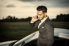 Knappe jonge mens door zijn auto met celtelefoon royalty-vrije stock afbeeldingen