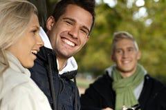 Knappe jonge mens en vrienden in park het glimlachen royalty-vrije stock foto