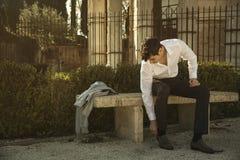 Knappe jonge mens in Europese stad, die op steenbank zitten Royalty-vrije Stock Foto
