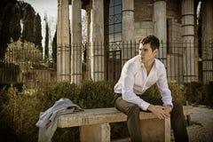 Knappe jonge mens in Europese stad, die op steenbank zitten Royalty-vrije Stock Afbeelding