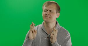 Knappe jonge mens in grijze sweater die gelukkig gebaar doen Gekruiste vingers royalty-vrije stock foto's