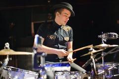 Knappe jonge mens in het drumstel van hoedenspelen Stock Foto