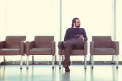 Knappe jonge mens met dreadlocks die zijn digitale tabletpc met behulp van bij een luchthavenzitkamer, moderne wachtkamer, met ba Royalty-vrije Stock Afbeeldingen